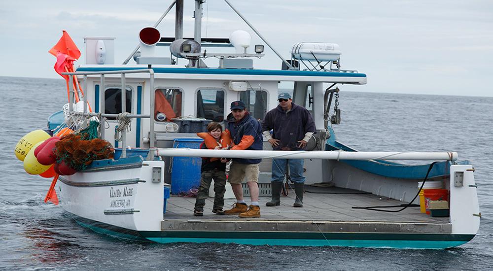 MANCHESTER BY THE SEA: Çocuk Patrick (Ben O'Brien) ve hayatının en güzel yıllarını sürmekte olan amca Lee (Casey Affleck) köpekbalığı şakasını bir kenara bırakıp oltalarına vuran asıl balığı tekneye çekerlerken arkada da baba Joe (Kyle Chandler) onları dikkatle izliyor. (Görüntü Yönetmeni: Jody Lee Lipes)